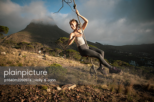 Blond woman swings on a rope on a slope - p1640m2260974 by Holly & John