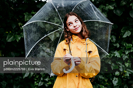 Thoughtful girl smiling while holding umbrella against leaf wall - p300m2225769 by Eva Blanco