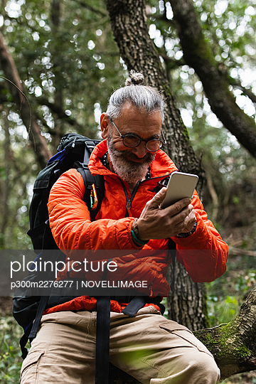 Smiling senior man using mobile phone in forest during weekend - p300m2276277 by NOVELLIMAGE