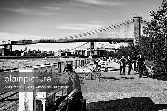 United States;  USA;  New York City;  Brooklyn;  Playing piano by Brooklyn Bridge - p566m1433323 by Antonino Bartuccio