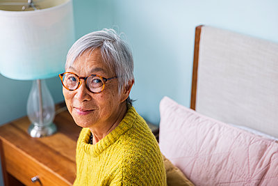Smiling senior woman wearing yellow sweater sitting in bedroom at home - p1166m2285612 by Cavan Images