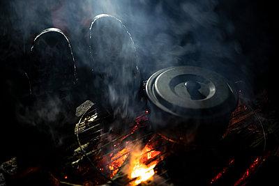 Man warms his feet at fireplace - p1687m2278483 by Katja Kircher