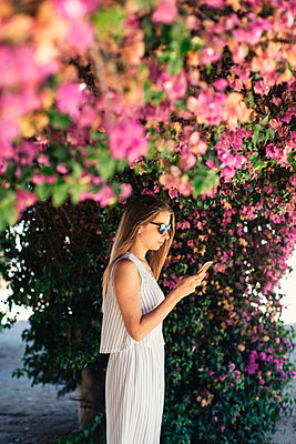 Woman using cell phone in park under pink blossoms - p300m2023837 by Javier Pardina