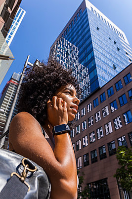 Germany, Frankfurt, portrait of young woman with smartwatch on the phone in front of skyscrapers - p300m2030316 by Tom Chance