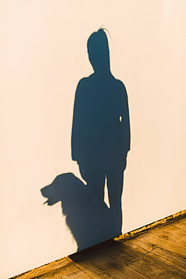 Shadow of a woman and her dog on a white wall - p300m2069533 by Ramon Espelt