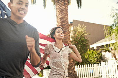 Portrait of young man and woman (23-30) running down the street, holding the stars and stripes flag, Los angeles, USA - p300m2264542 von LOUIS CHRISTIAN