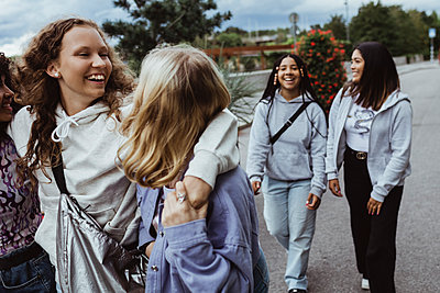 Cheerful female friends talking while walking on footpath - p426m2259434 by Maskot