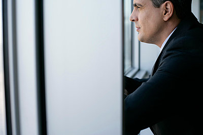 Businessman looking through a window - p4733574f by Stock4B