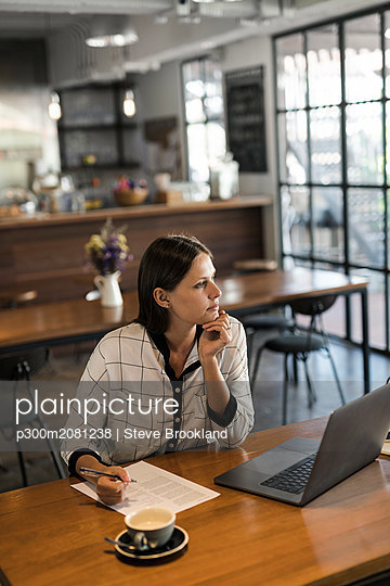 Young businesswoman in a cafe writing on paper and working with laptop on wooden table - p300m2081238 by Steve Brookland