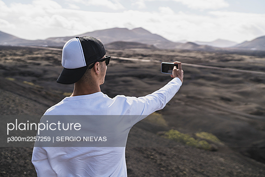 Male tourist in hat taking selfie at El Cuervo Volcano during vacations, Lanzarote, Spain - p300m2257259 by SERGIO NIEVAS