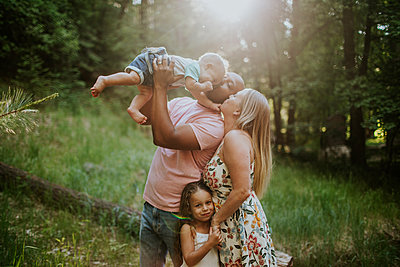 Family of four snuggling and kissing in forest - p1166m2201902 by Cavan Images