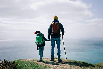 father and son stood at the top of the Jurassic coast in Dorset, UK - p1166m2279481 by Cavan Images