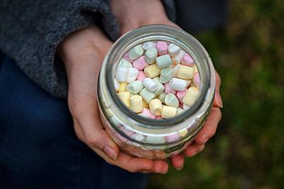 Hands holding glass of marshmallows, close-up - p300m1581578 von Lisa und Wilfried Bahnmüller