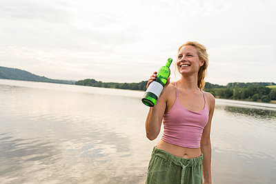 Happy young woman drinking water at a lake - p300m2140581 by Joseffson