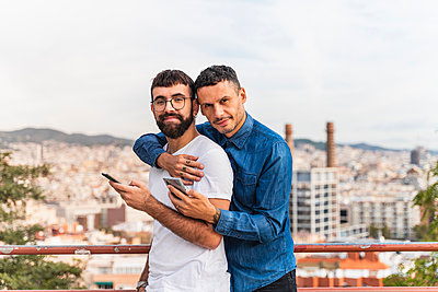 Portrait of happy gay couple with smartphones, Barcelona, Spain - p300m2155118 by VITTA GALLERY