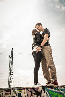Teenage couple kissing on a graffiti wall - p300m2206555 by Studio 27