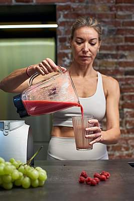 Mature woman pouring raspberry fruit smoothie in glass at kitchen - p300m2241830 by Veam