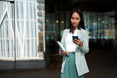 Female professional text messaging on mobile phone - p300m2276686 by Veam