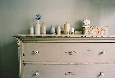 Painted vintage style chest of draws in a bedroom with personal belongings - p349m695136 by Emma Lee