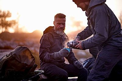Hiker pouring coffee into friend's cup, Sarkitunturi, Lapland, Finland - p429m1188268 by Aleksi Koskinen