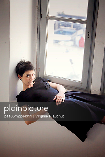 Woman in black dress on windowsill, portrait - p1105m2244911 by Virginie Plauchut