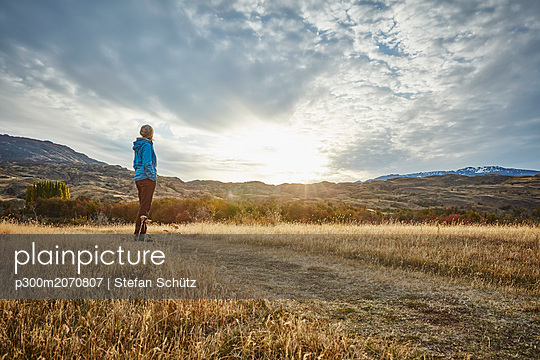 Chile, Valle Chacabuco, Parque Nacional Patagonia, woman standing in steppe landscape at sunset - p300m2070807 by Stefan Schütz