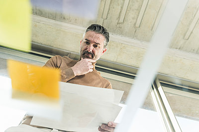 Mature businessman working on adhesive notes on glass table in office - p300m2160717 by Uwe Umstätter