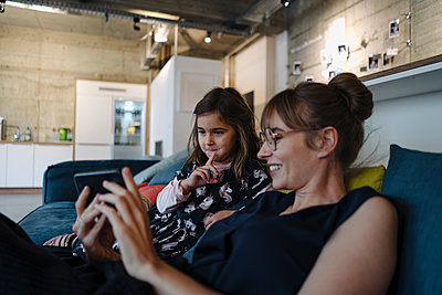 Woman and girl sitting on couch in office using smartphone - p300m2167336 by Kniel Synnatzschke
