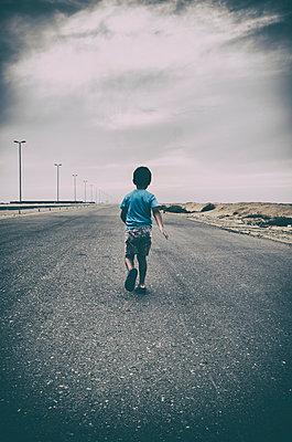 Little boy walking in an empty road  - p794m966726 by Mohamad Itani