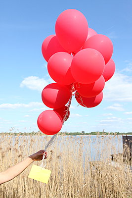 Woman with red balloons - p045m931642 by Jasmin Sander