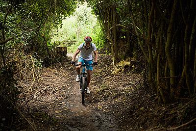 Mature man mountain biking on trail in woods - p1023m2009579 by Trevor Adeline