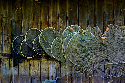 Germany, Bavaria, Diessen am Ammersee, Fishing nets hanging at boathouse - p300m2256131 by Lisa und Wilfried Bahnmüller