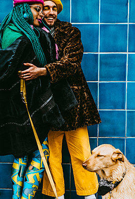 Smiling young man hugging woman while standing with dog against blue tiled wall - p426m2279789 by Maskot