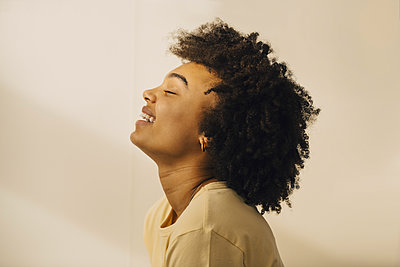 Side view of curly haired woman with eyes closed against beige wall - p426m2284654 by Maskot