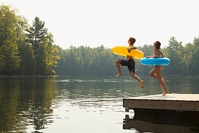 Kids jumping off end of dock holding inflatable rings on Crystal Lake; Ontario, Canada - p442m1086642 by Vast Photography