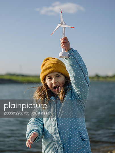 Cheerful girl holding toy windmill screaming while standing against Rhine river during sunny day - p300m2206733 by Gustafsson