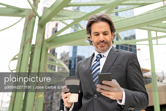 Businessman holding coffee cup while using mobile phone against structure - p300m2277191 by Jose Carlos Ichiro