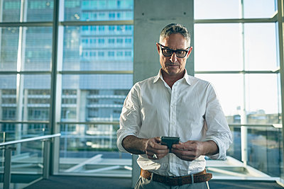 Businessman watching his mobile phone - p1315m2090969 by Wavebreak
