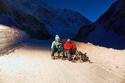 Couple sledding in snow-covered landscape at night - p300m1588192 von Christian Vorhofer