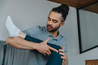 Physiotherapist holding knee of female patient while giving therapy in medical practice - p300m2275983 by Mareen Fischinger