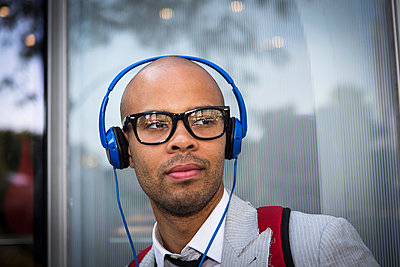 Portrait of young man with shaved head wearing headphones - p924m836702f by Steve Prezant