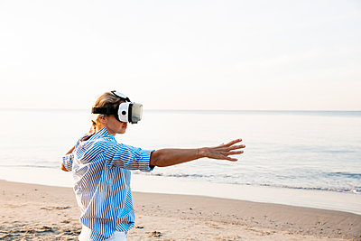 Blonde woman doing kind of yoga exercises on a beach in thailand with 3D virtual reality goggles - p300m2080380 by Epiximages
