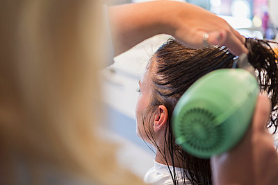 Caucasian stylist drying hair of woman - p555m1522944 by Marc Romanelli