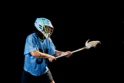 Young male lacrosse player poised with lacrosse stick, against black background - p924m2077888 by Edwin Jimenez