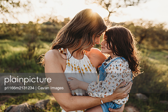 Young mother holding daughter and cuddling in bright california field - p1166m2131234 by Cavan Images