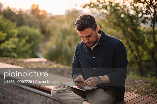 Businessman using smart phone while sitting on bench in park - p1166m2292729 by Cavan Images