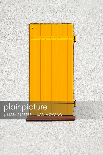 Window with a yellow shutter - p1423m2125769 von JUAN MOYANO
