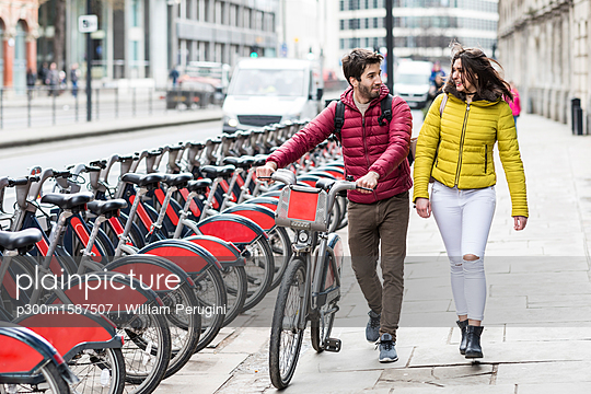 UK, London, young couple with bicycle from bike share stand walking in city - p300m1587507 von William Perugini