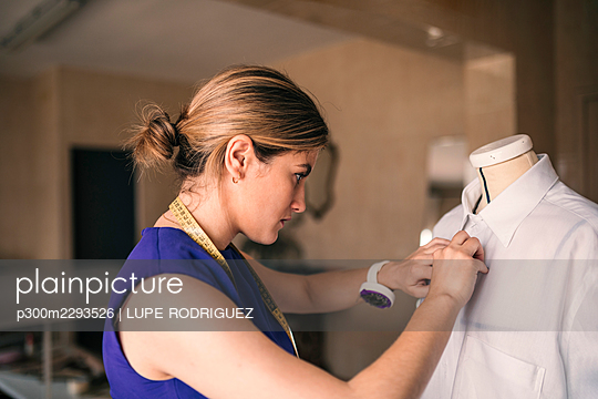 Female fashion designer buttoning mannequin shirt at workshop - p300m2293526 by LUPE RODRIGUEZ