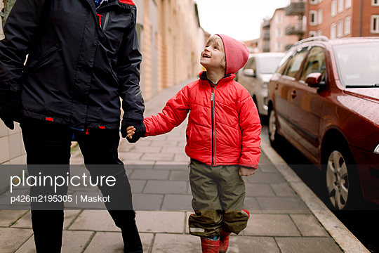 Smiling grandson in warm clothing holding hands of grandmother while walking on footpath - p426m2195305 by Maskot
